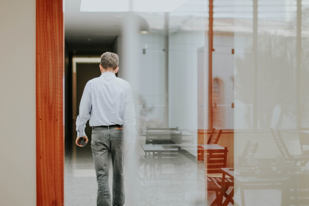 man in white dress shirt and gray denim jeans standing in front of glass window