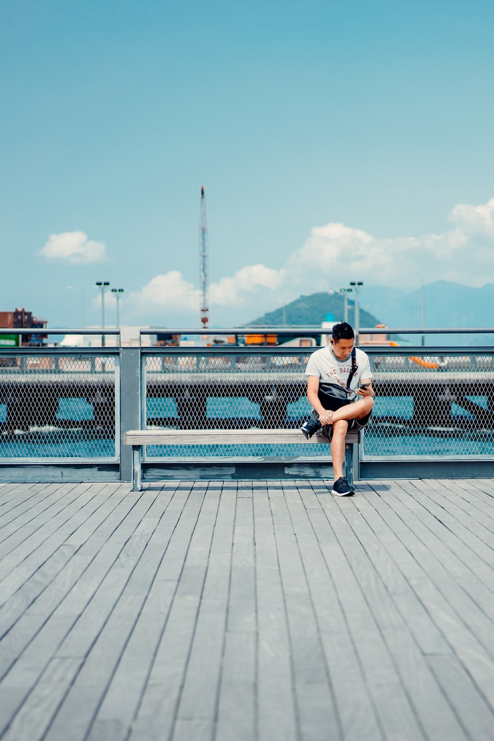 man in white t-shirt and blue shorts sitting on white metal fence during daytime