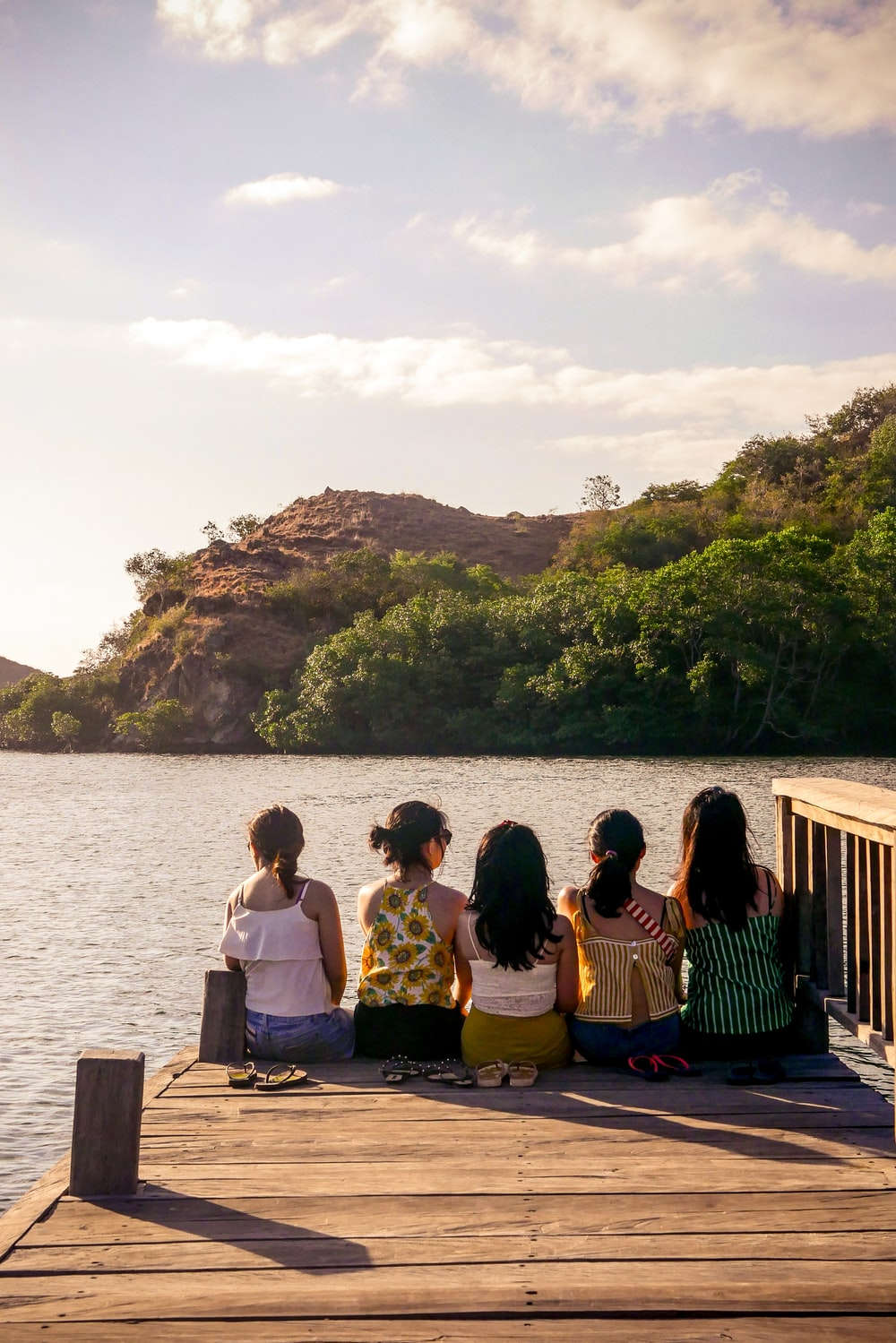 group of people sitting on brown wooden bench near body of water during daytime
