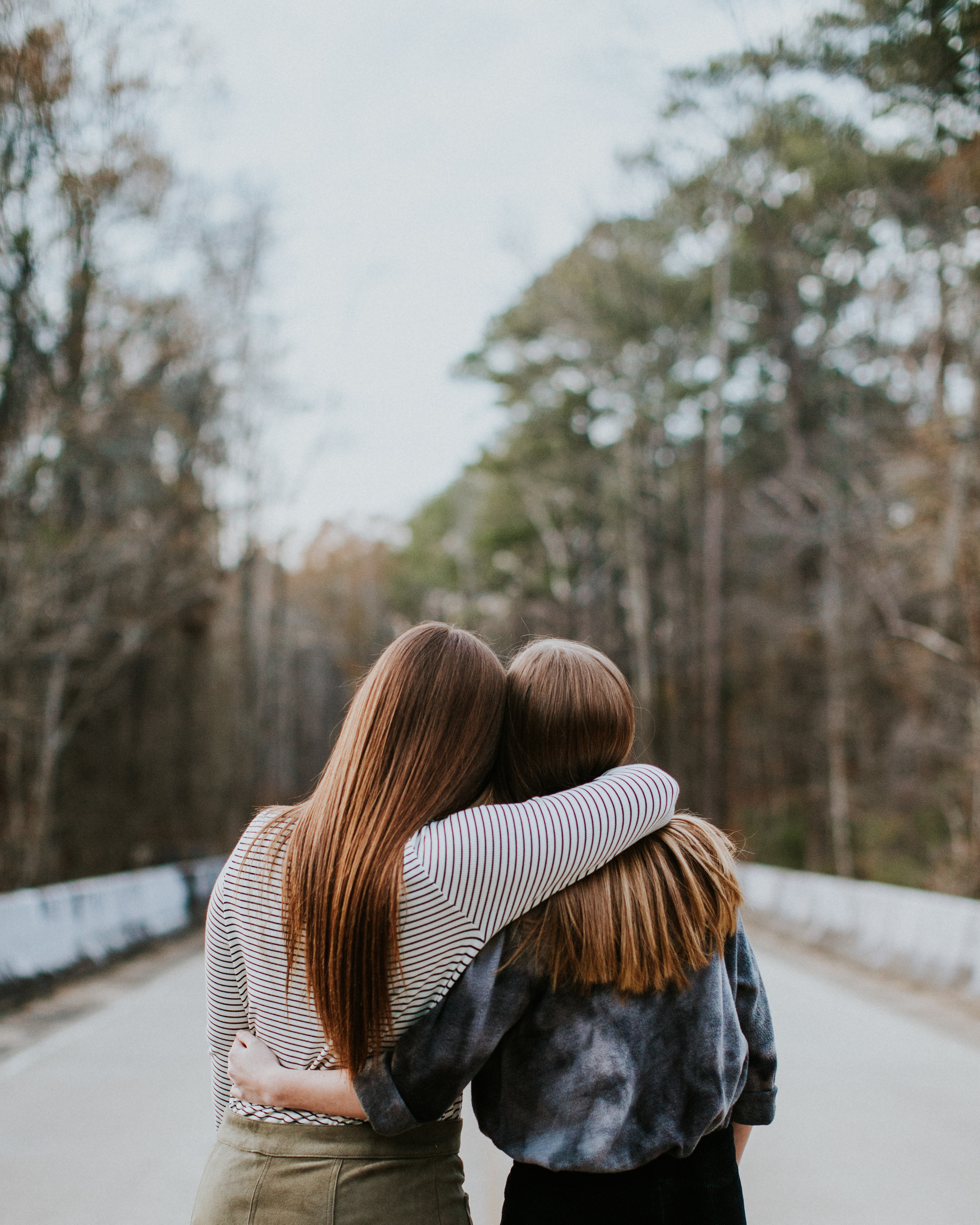 two girl best friends hugging each other facing opposite direction