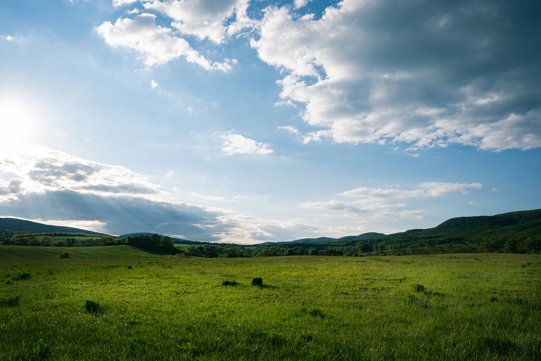 Spring Landscape with green field. Green fields and haystacks during the sunset, ray of light through the clouds at Hungary.