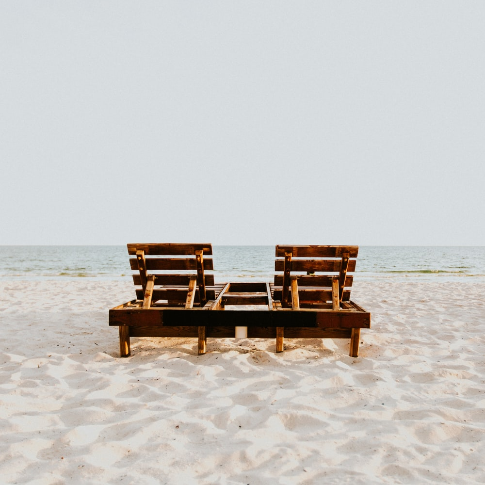 brown wooden chair on white sand beach during daytime
