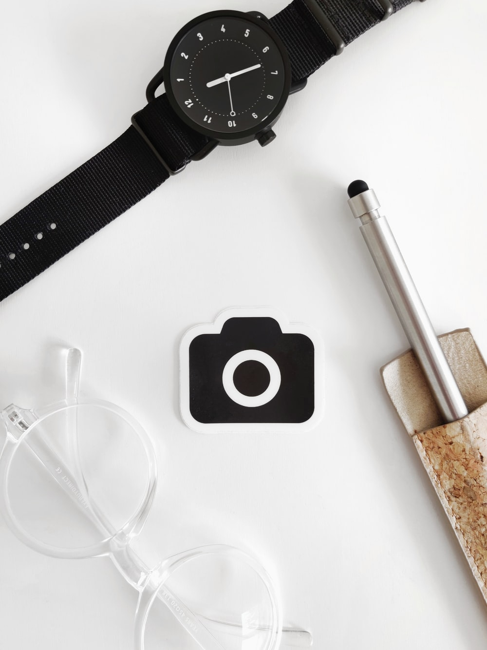 black round analog watch beside silver pen and white pen