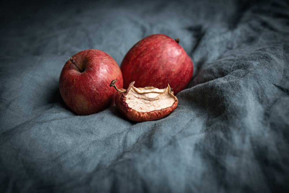 red apple fruit on gray textile