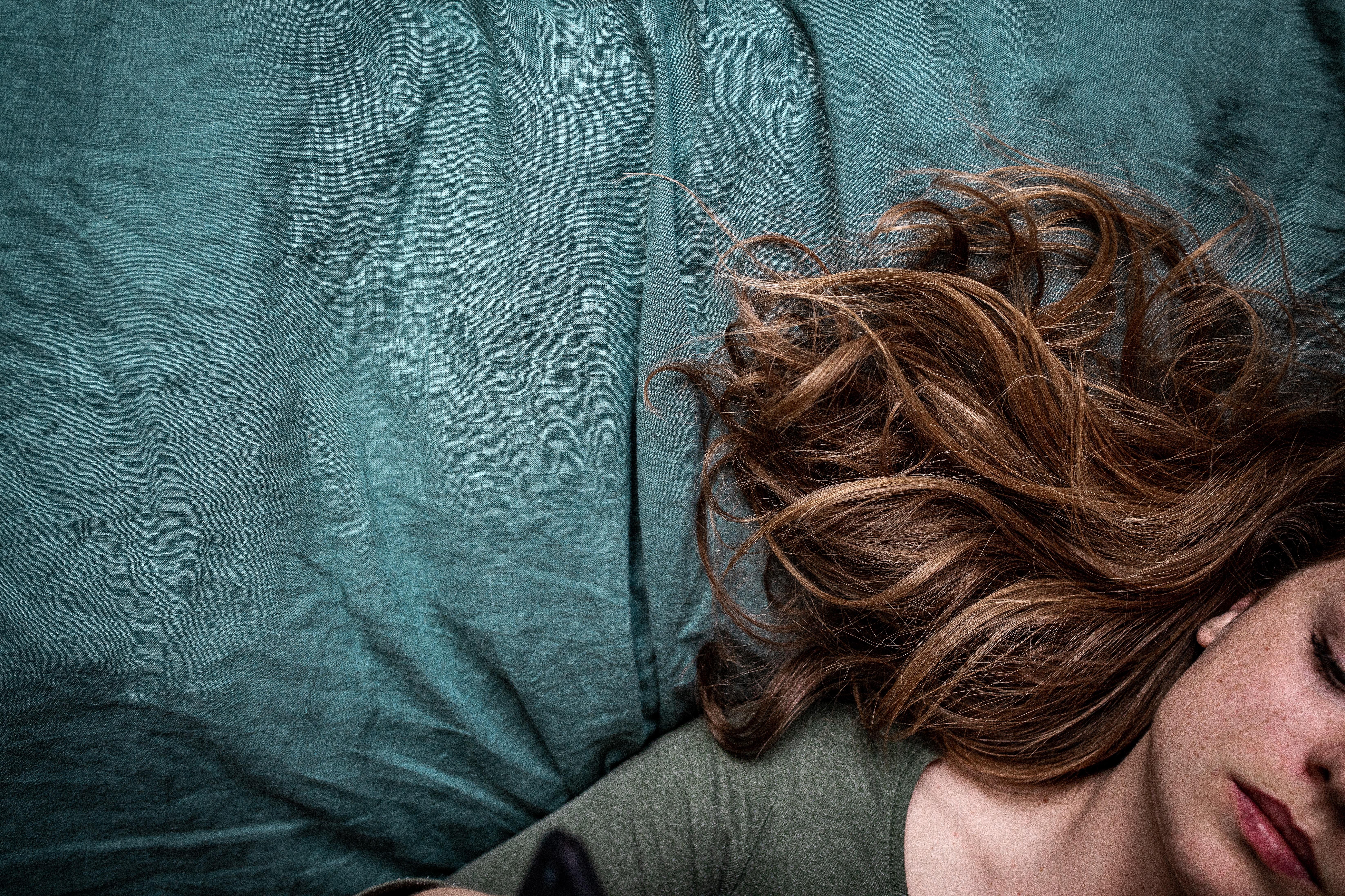 Girl lying on a green linen sheets