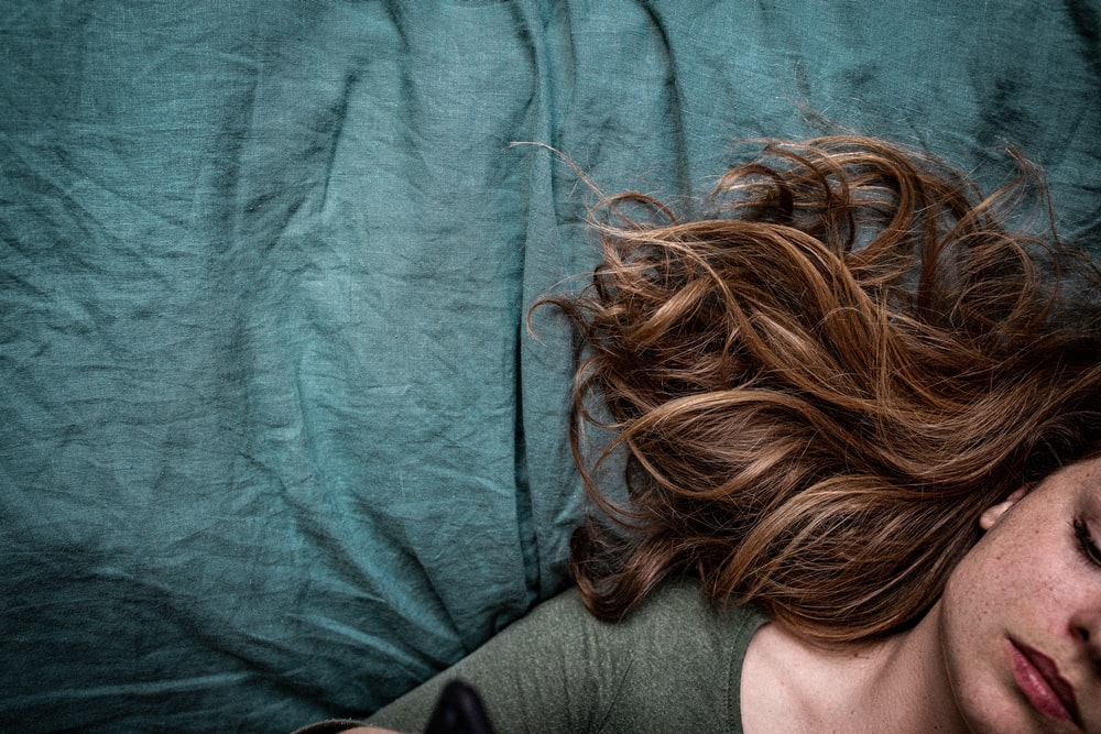 woman in gray shirt lying on blue textile