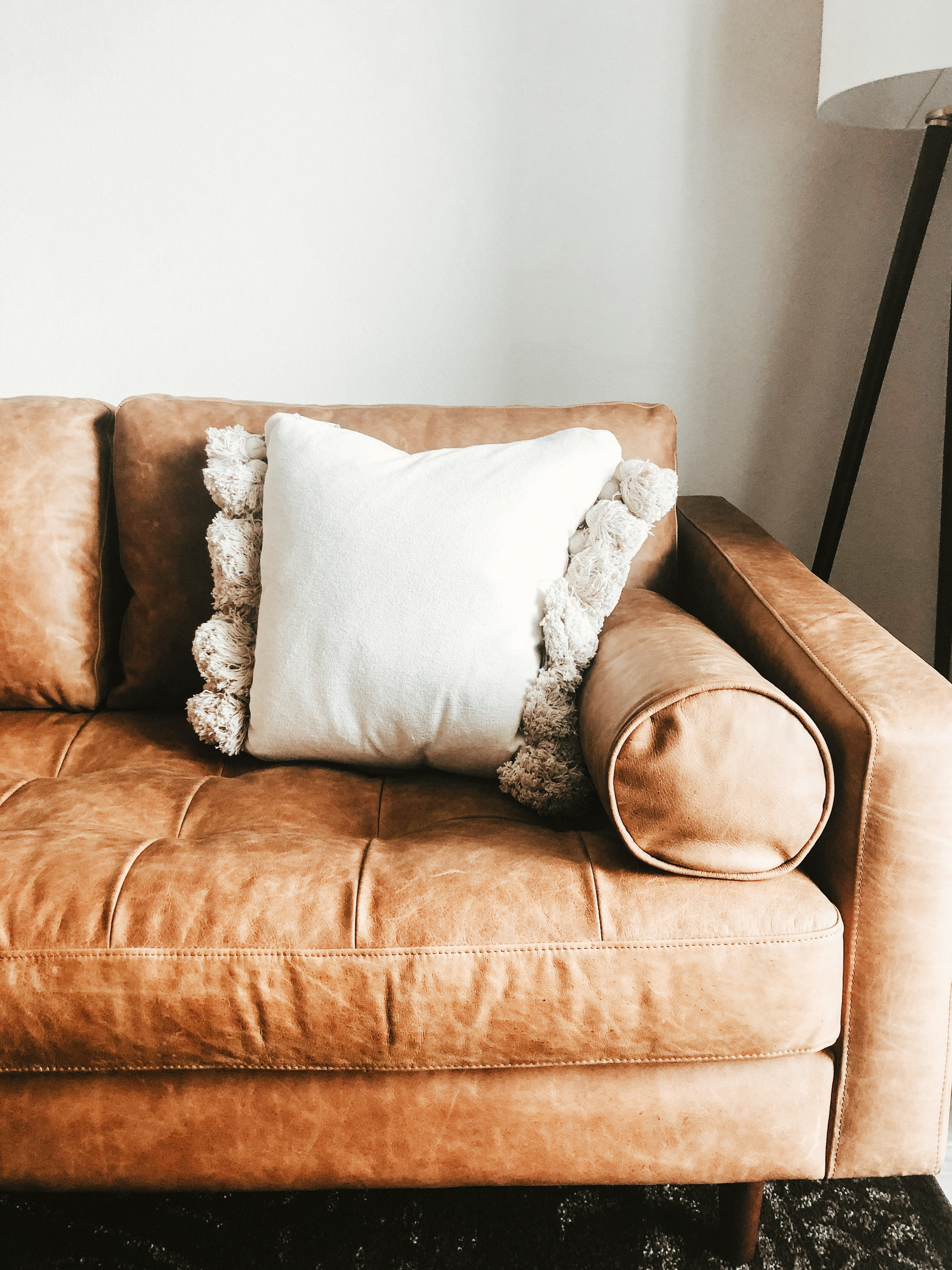 White pillow on a cozy leather couch.