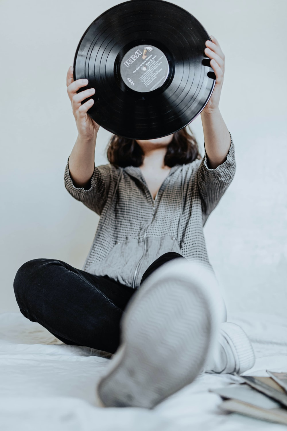 woman in white knit sweater and black pants holding black vinyl record