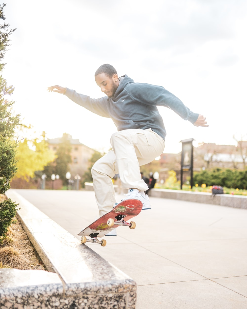 man in gray hoodie and brown pants riding skateboard during daytime