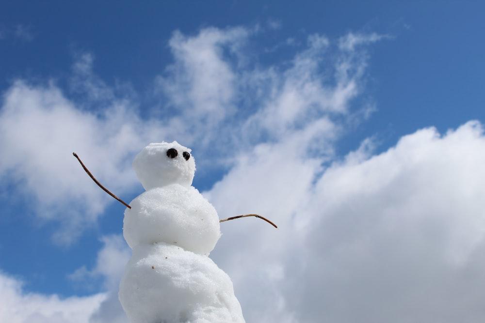 white snowman under blue sky during daytime