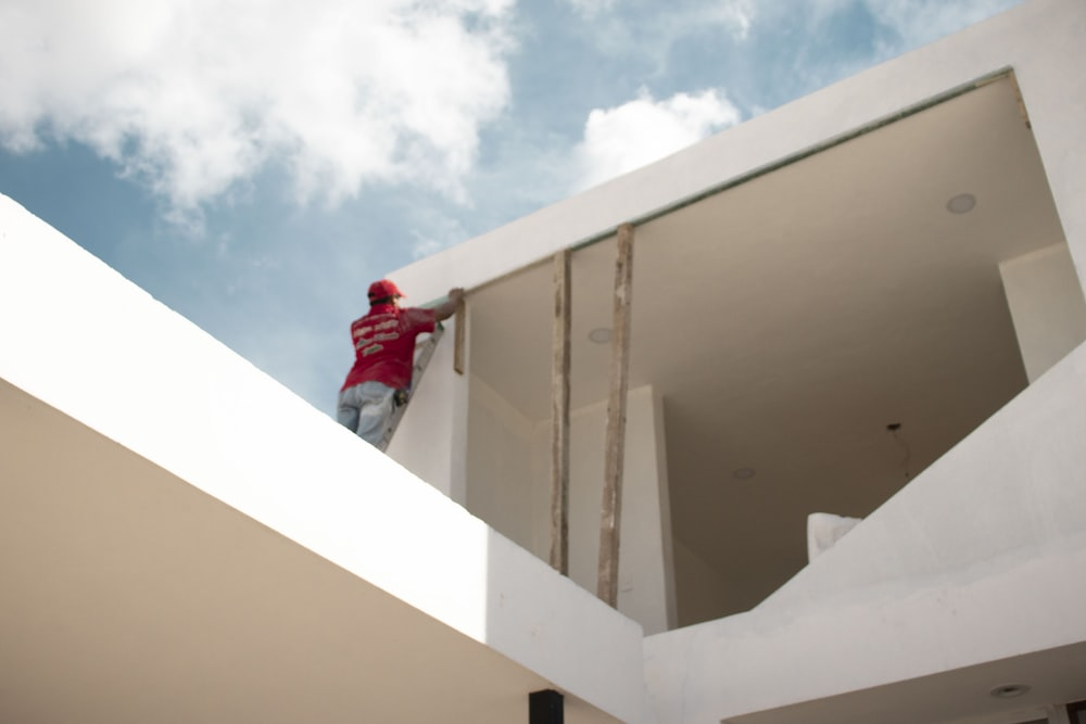 man in red jacket standing on white concrete building under blue and white cloudy sky during