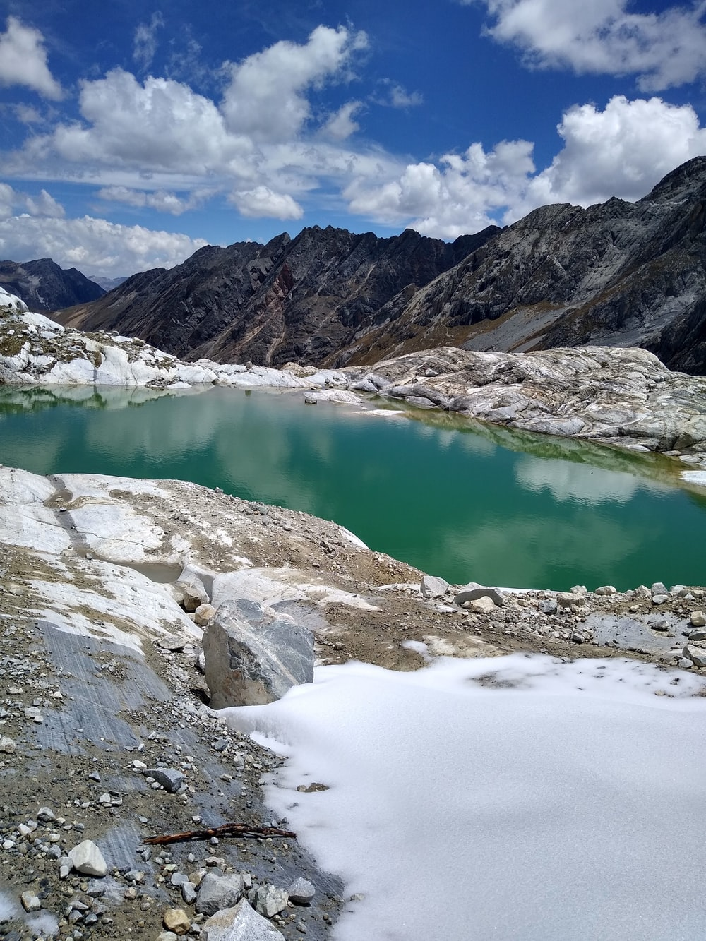 lake in the middle of mountains during daytime