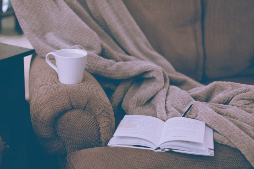 white ceramic mug on book page