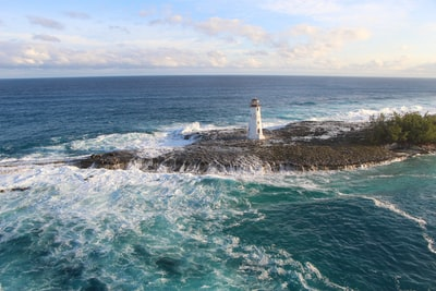 white lighthouse on brown rock formation on sea during daytime bahamas teams background