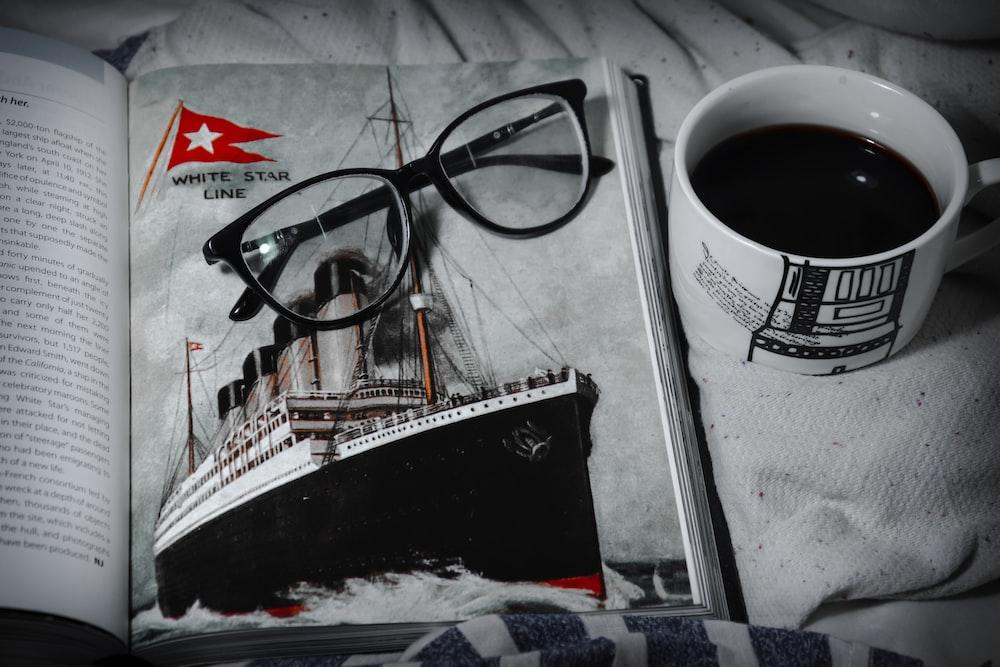 black framed eyeglasses on white and black boat print textile