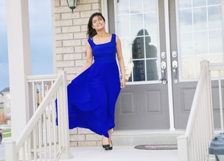 woman in blue sleeveless dress standing near white wooden door
