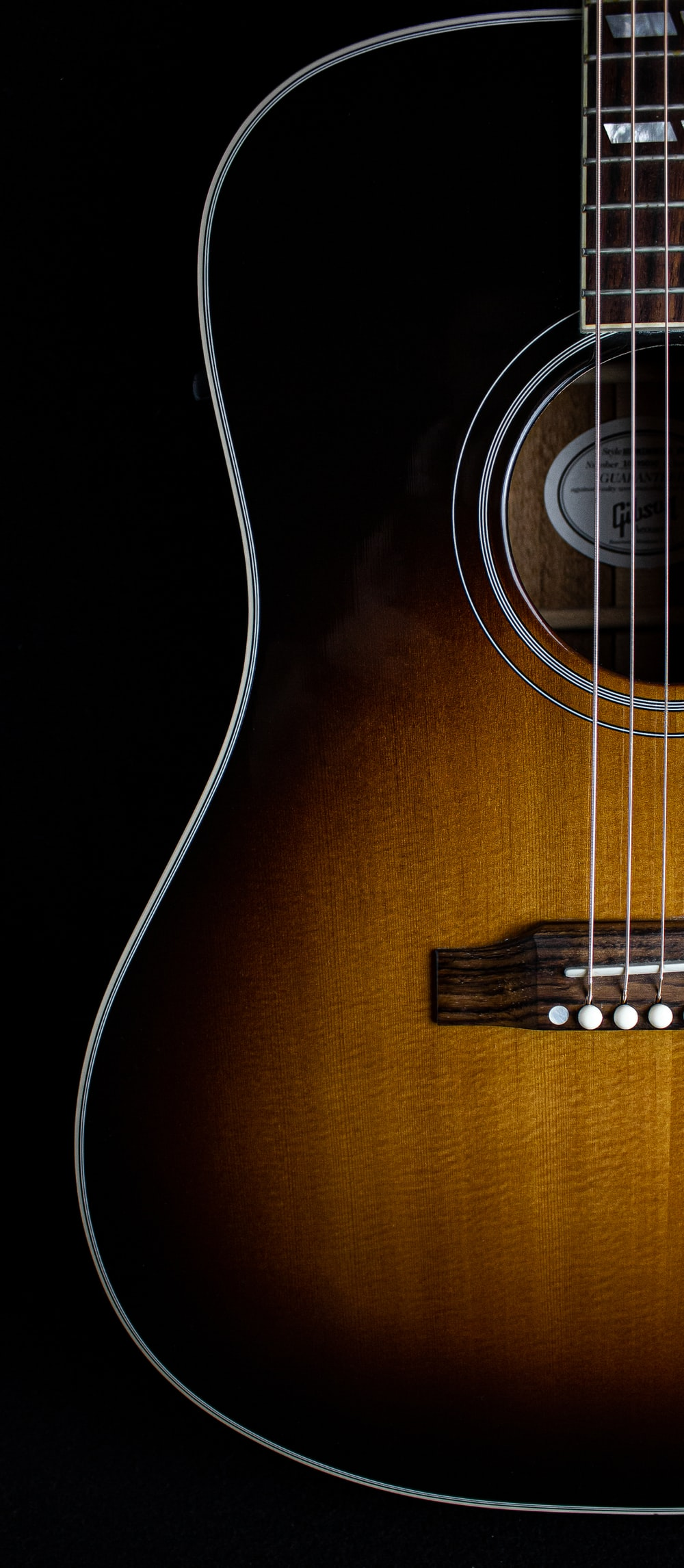 brown acoustic guitar on black background