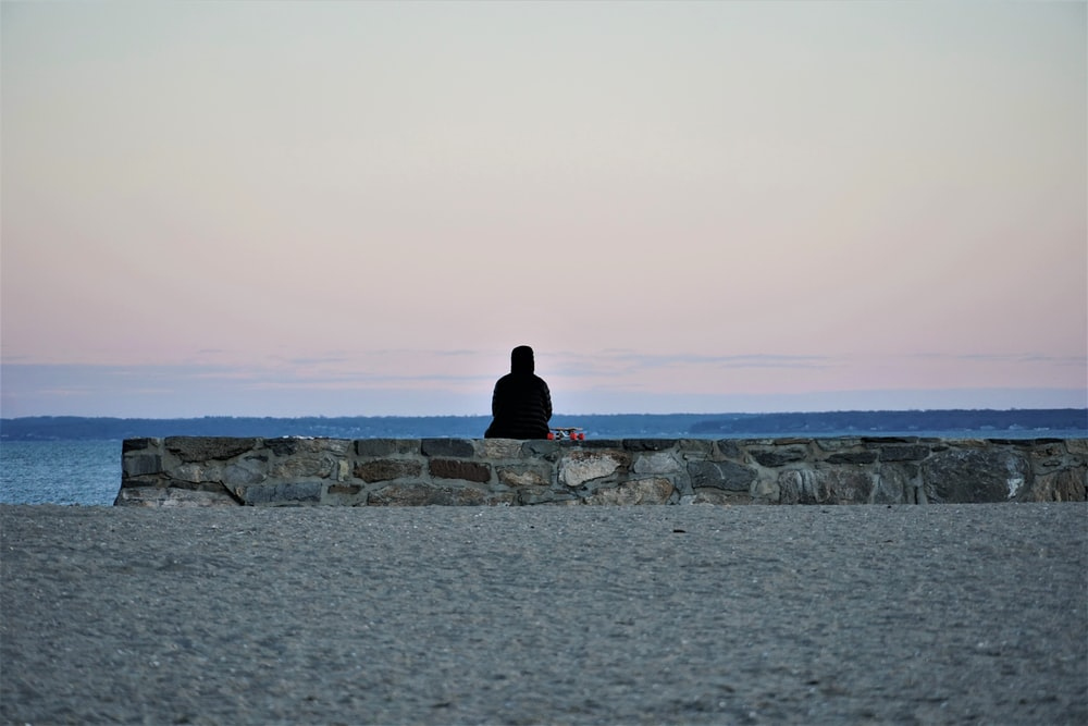 man in black jacket sitting on rock formation near sea during daytime
