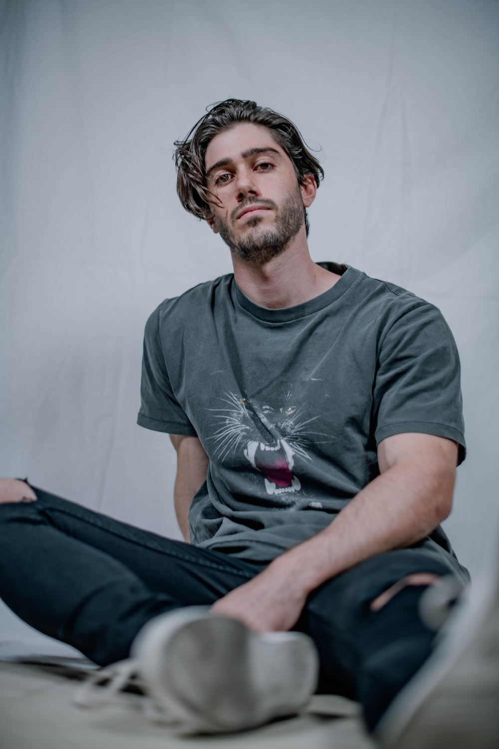 man in gray crew neck t-shirt sitting on bed