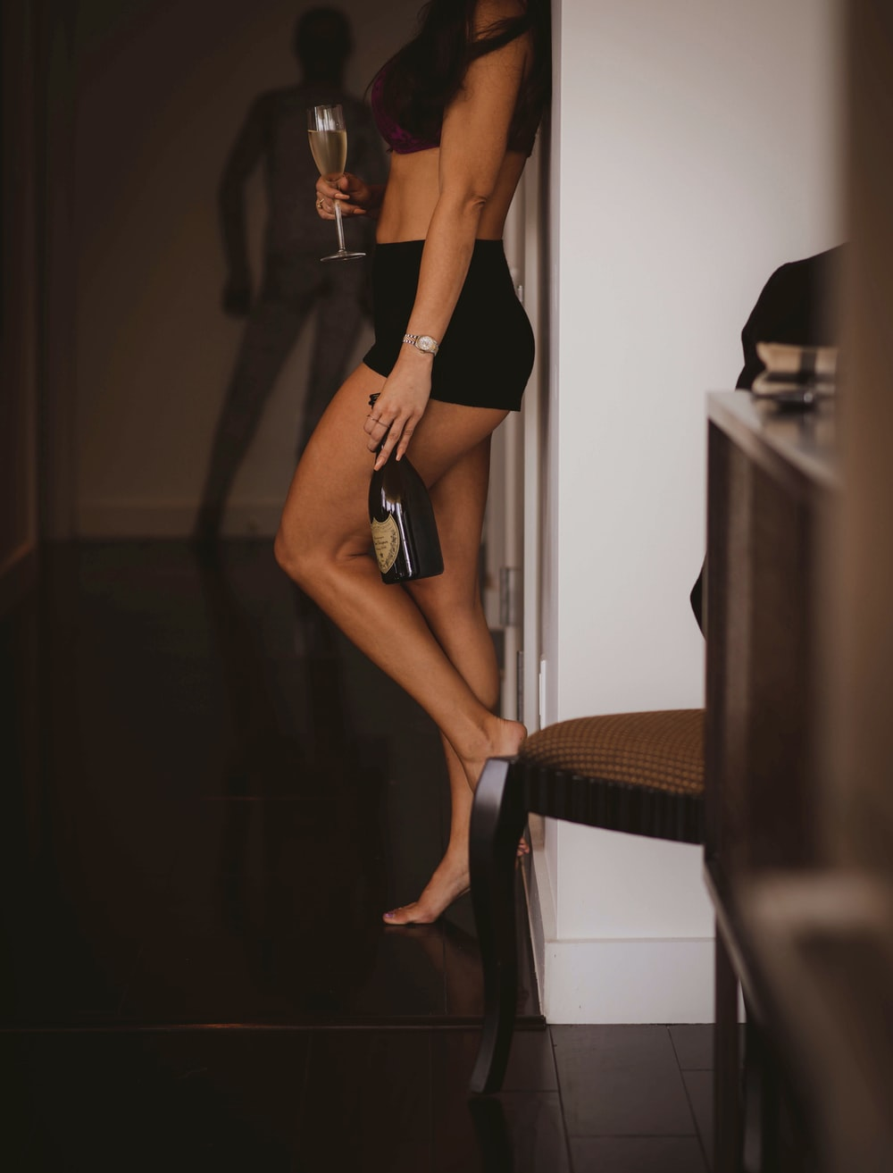 woman in black bikini bottom and black stockings standing on brown wooden staircase