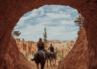 2 men riding horses on brown rock formation during daytime