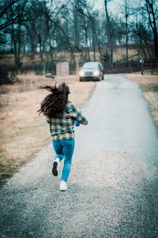 girl in blue denim shorts walking on gray asphalt road during daytime