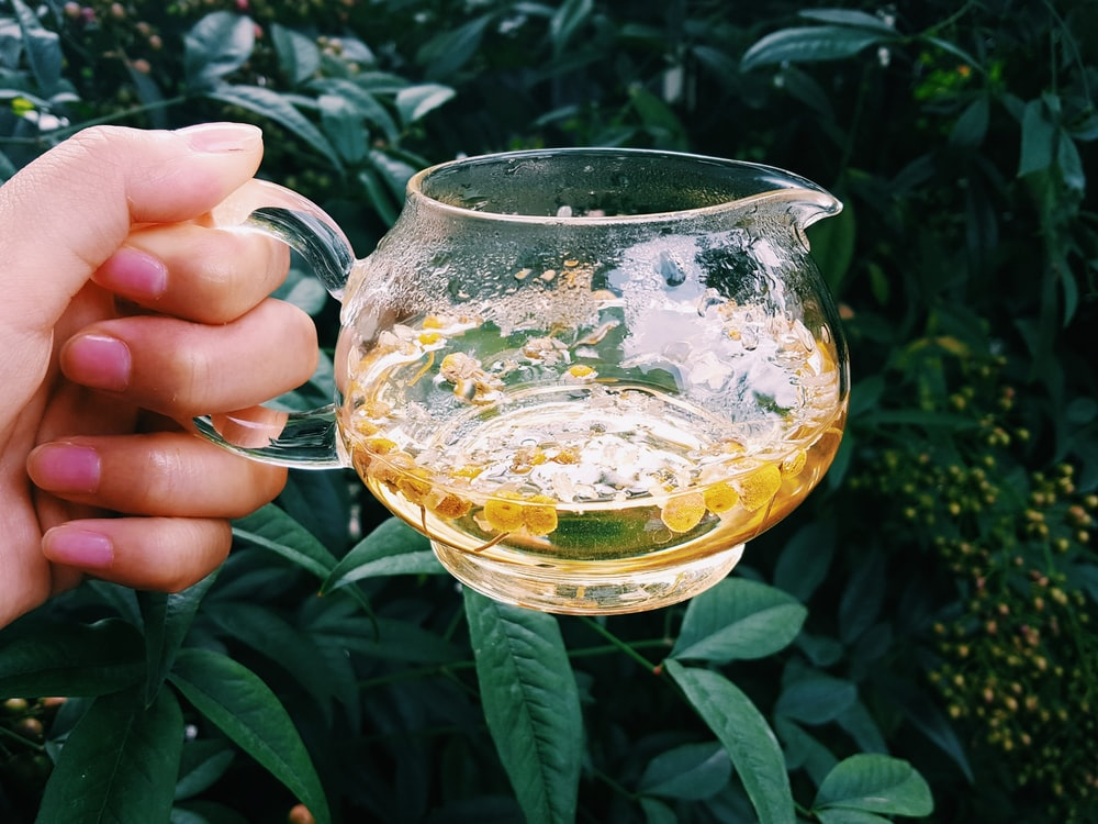 person holding clear glass mug with yellow liquid