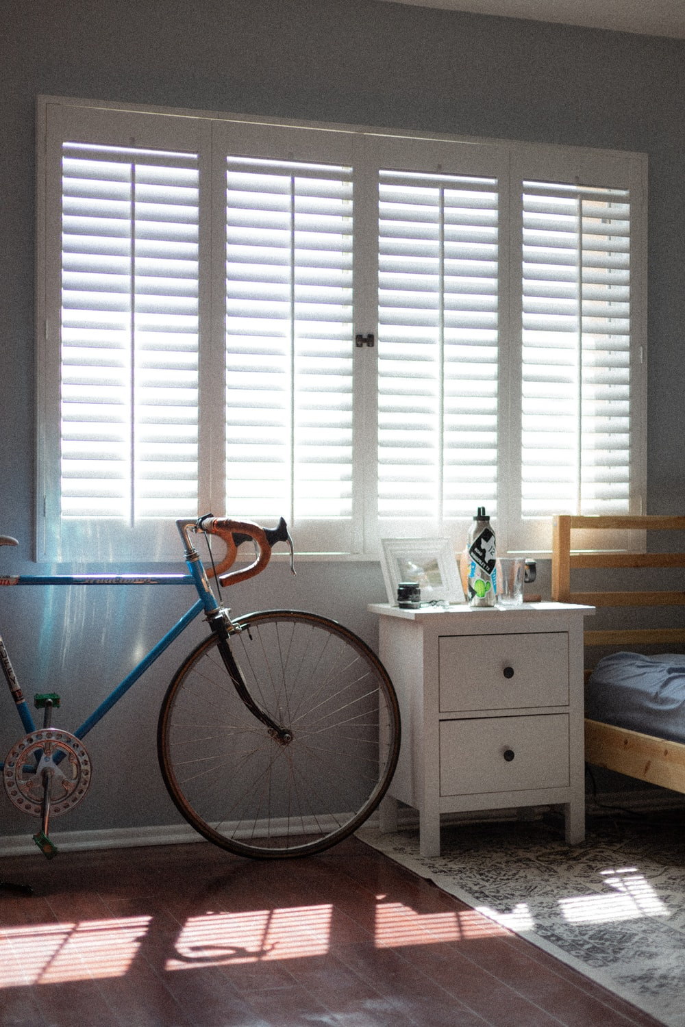 blue and black bicycle beside white wooden drawer