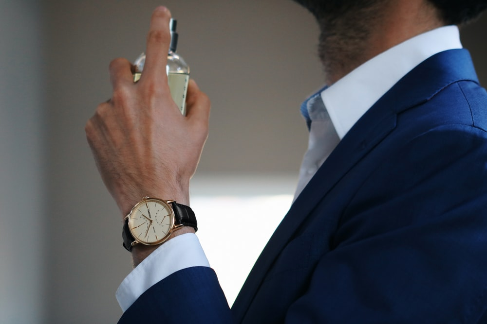 man in blue suit jacket wearing gold round analog watch