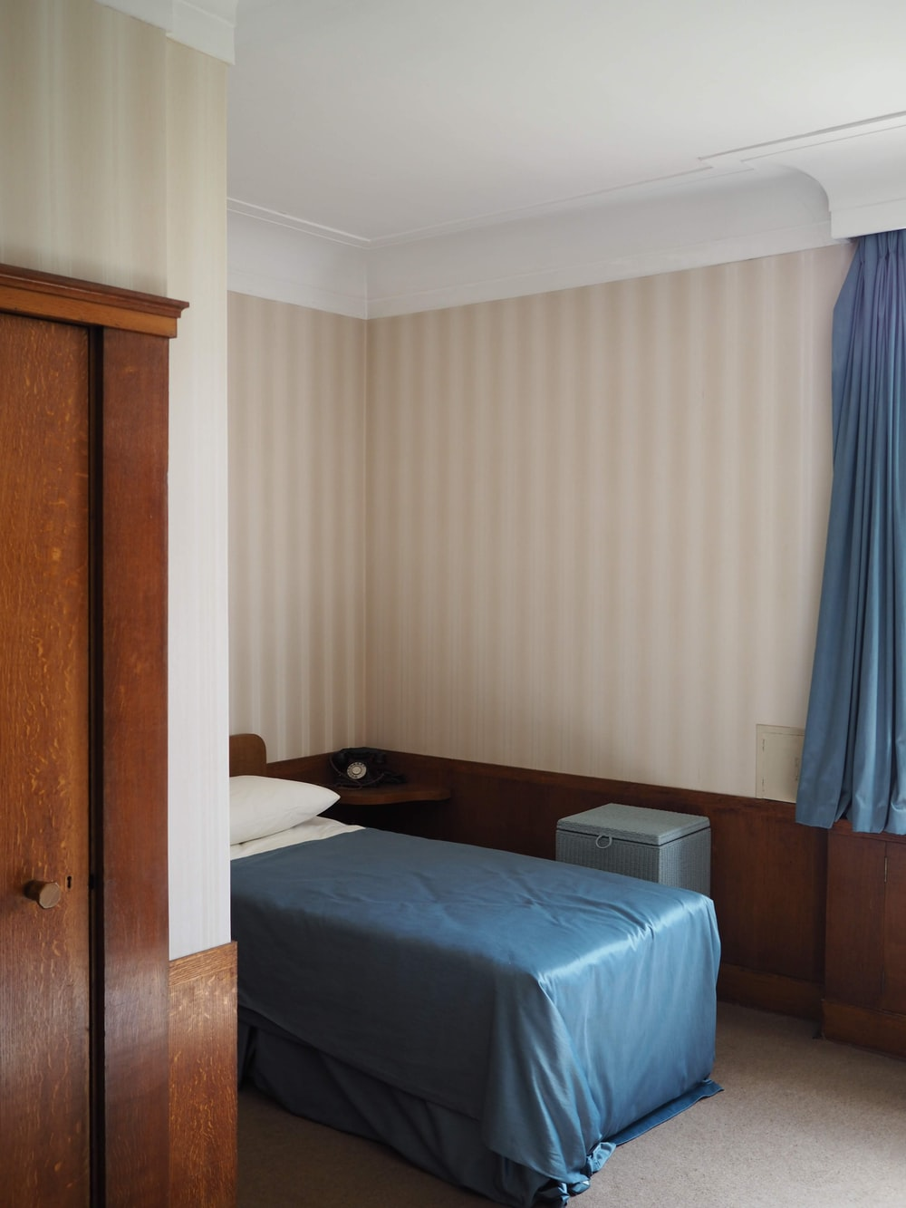 blue bed linen near brown wooden door