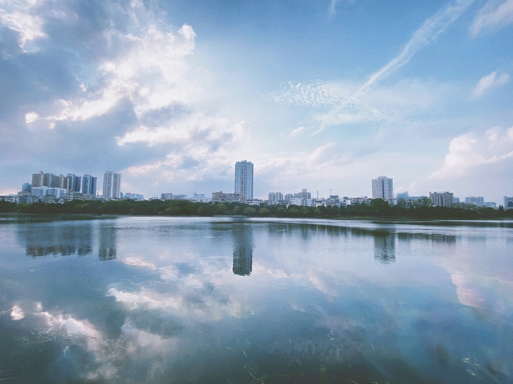 city skyline across body of water under blue and white sunny cloudy sky during daytime