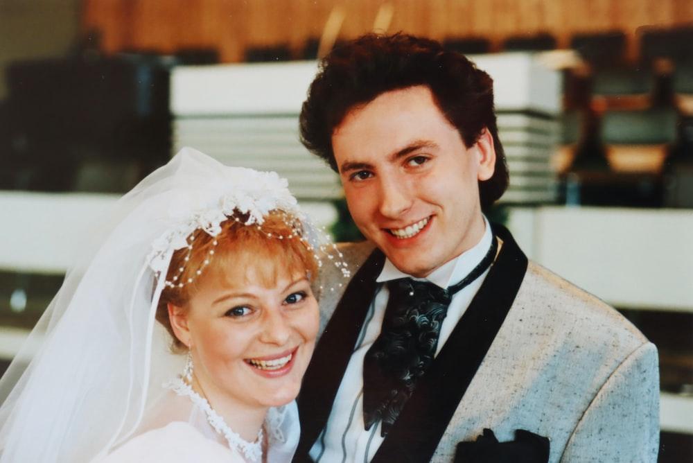 man in black suit beside woman in white floral wedding dress