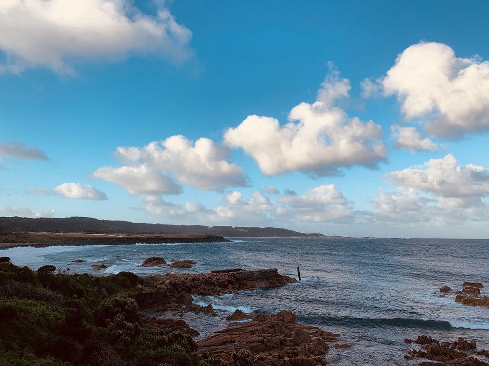 brown rock formation on sea under blue sky and white clouds during daytime