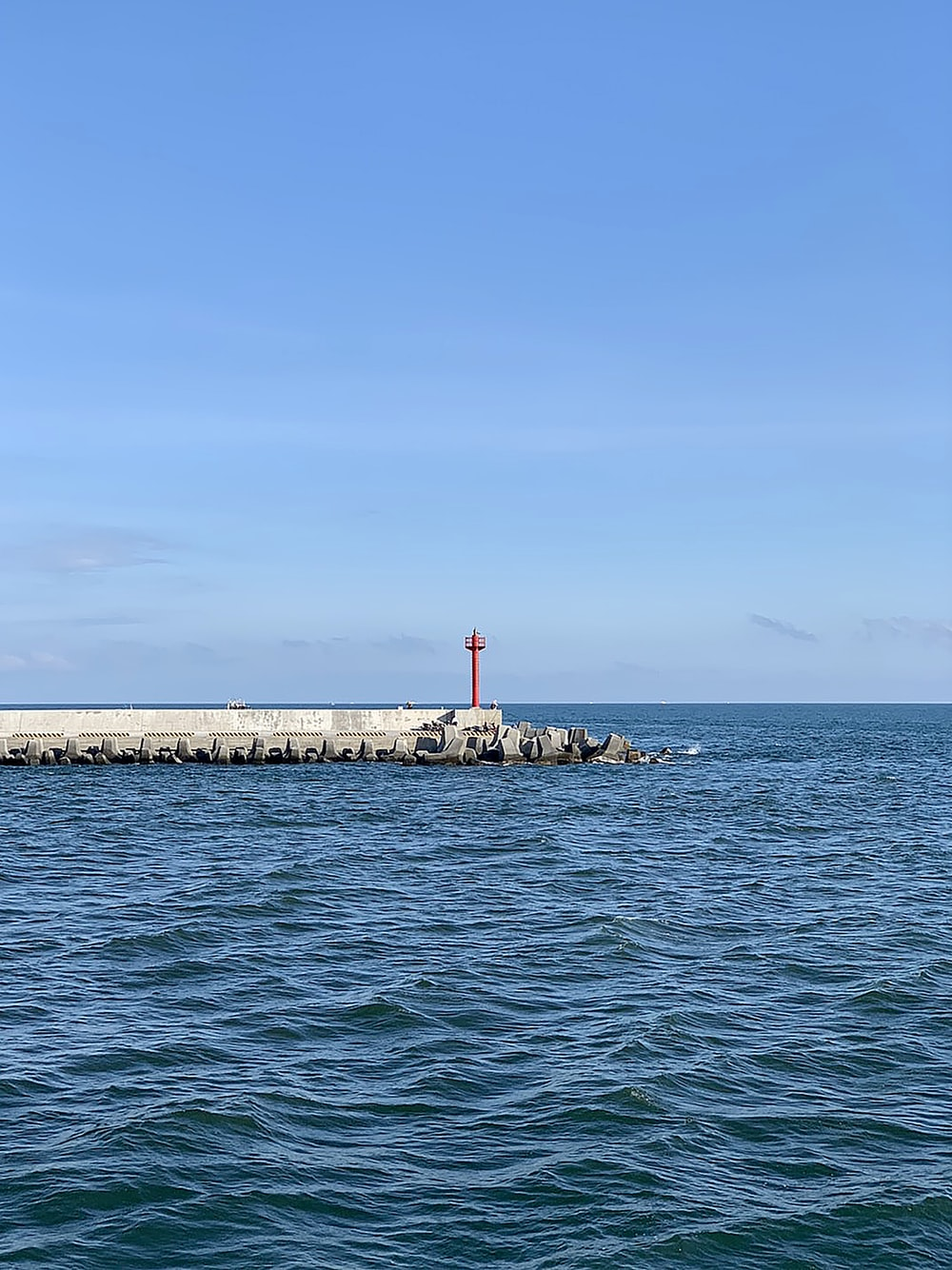 red and white lighthouse on the sea during daytime