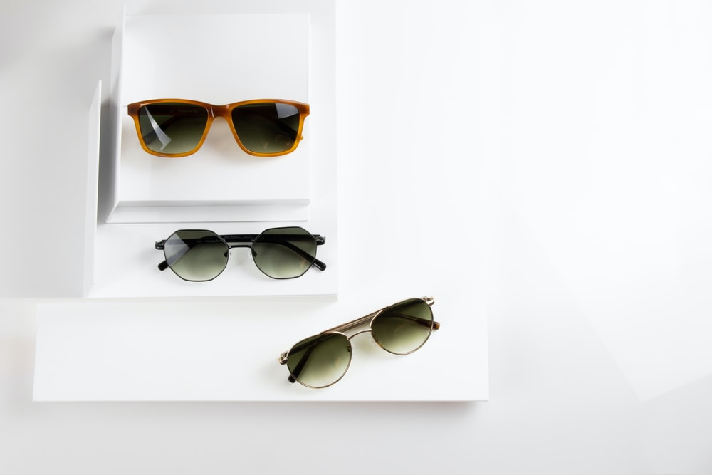 black framed sunglasses on white table