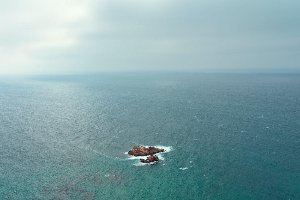 brown rock on blue sea under gray sky