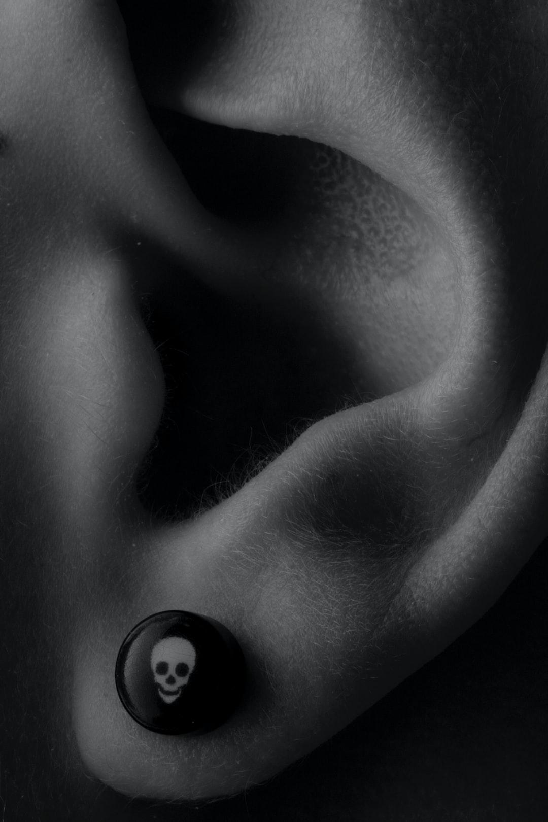 Detail shot of ear with skull earring