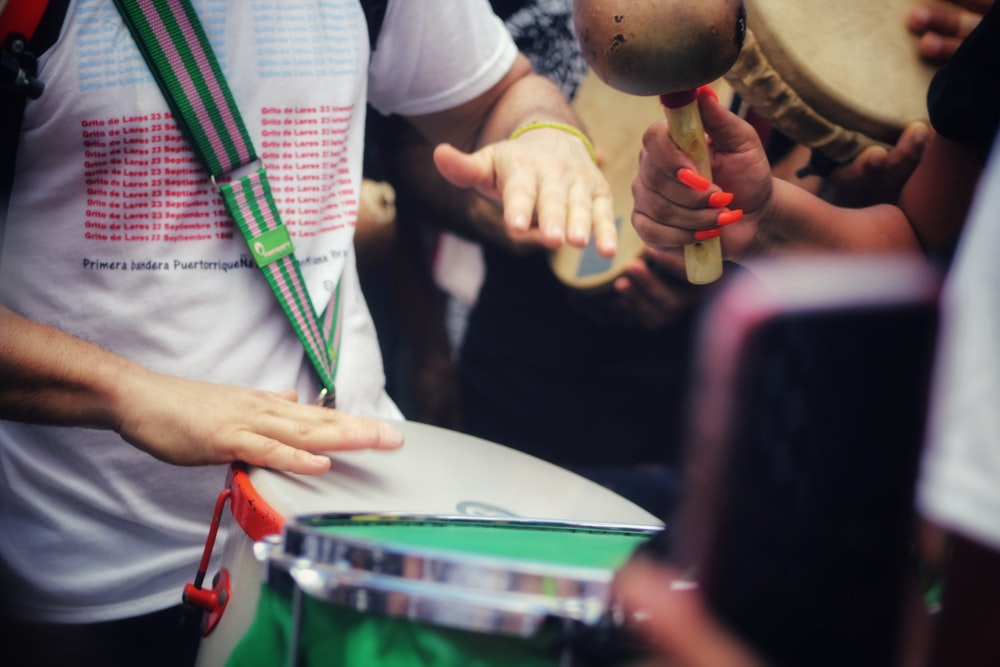 person in white long sleeve shirt holding drum stick