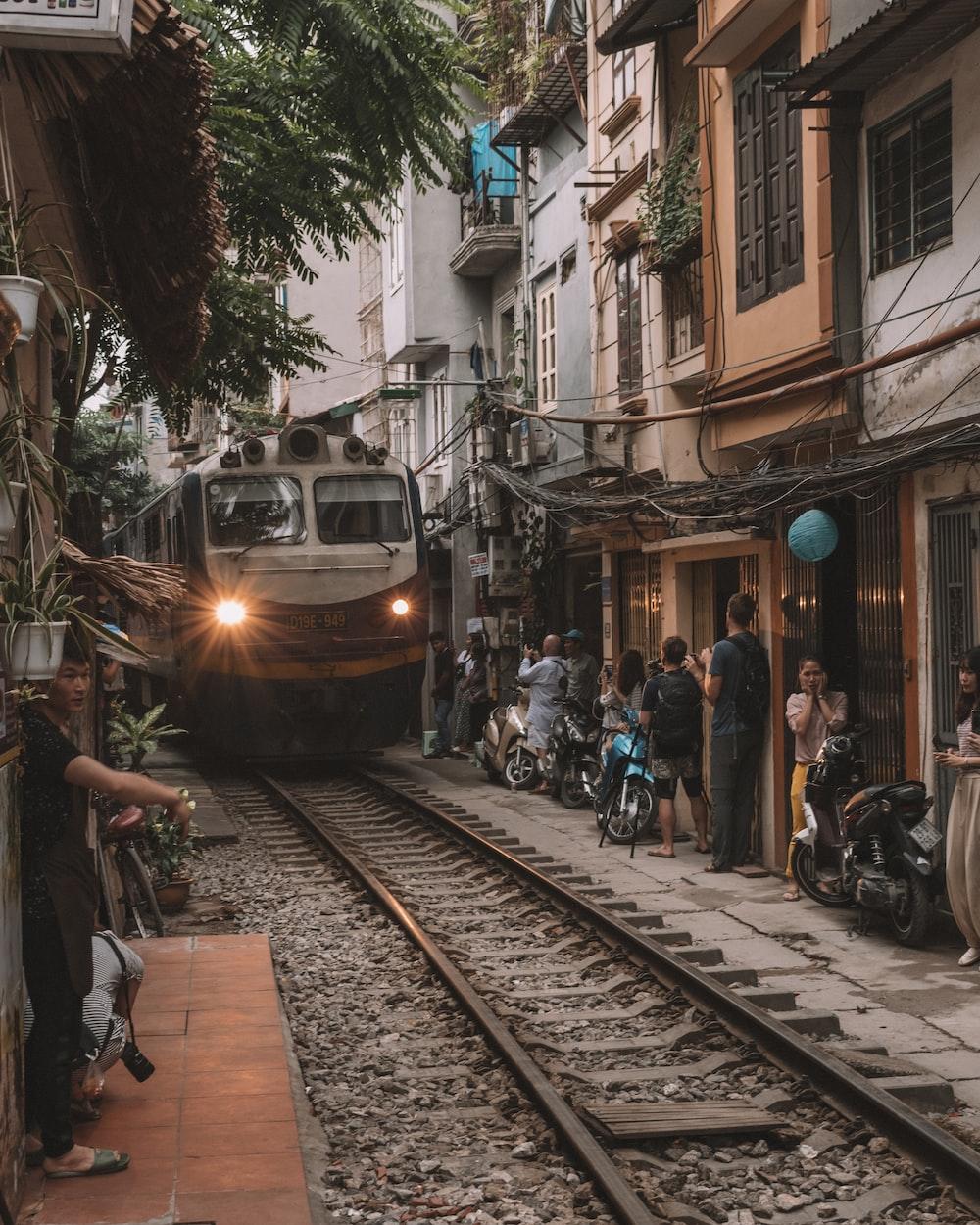 people walking on sidewalk near train during daytime