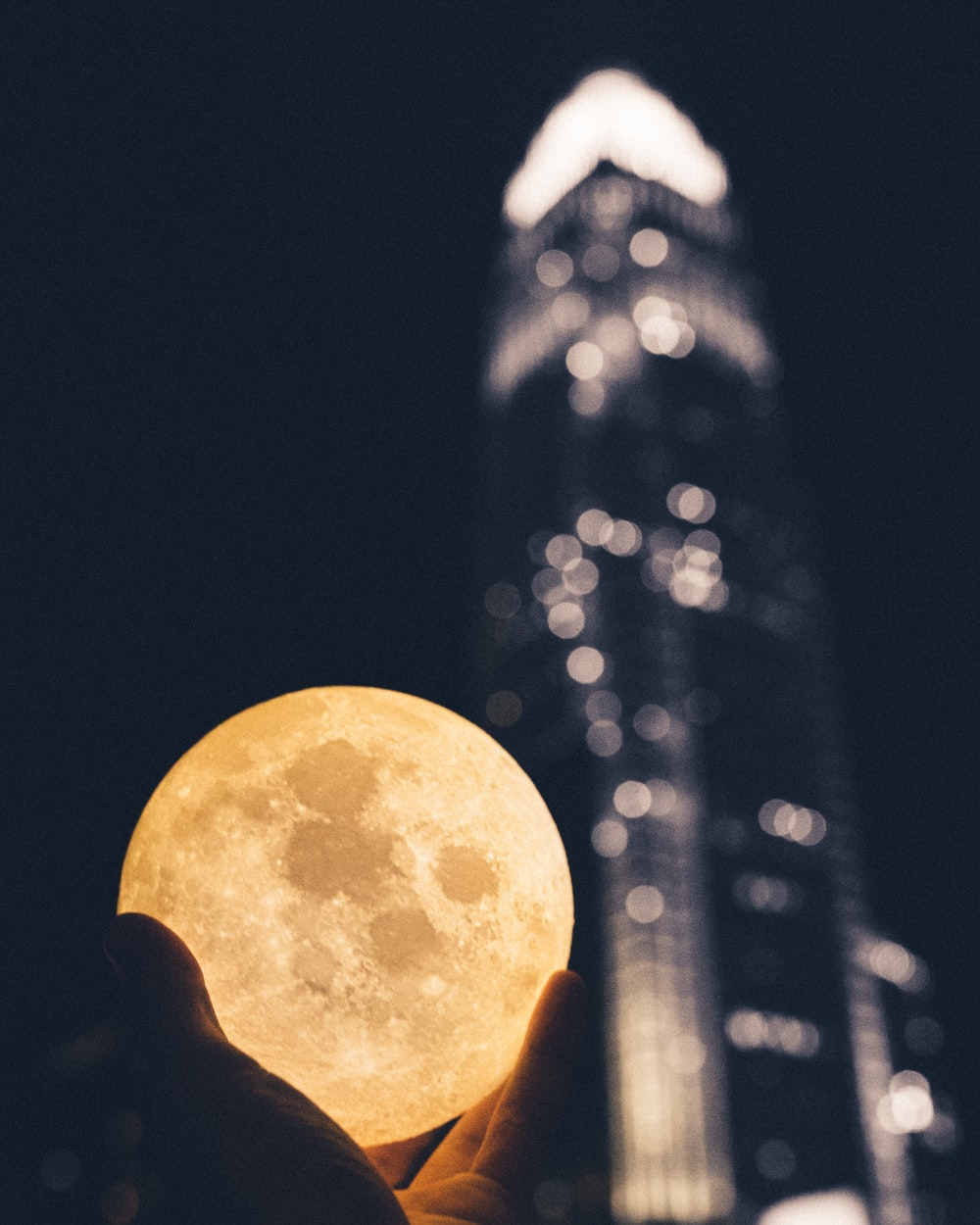 full moon over city buildings during night time