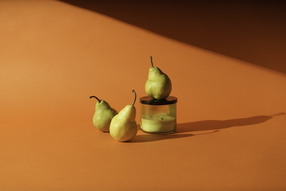 yellow pear fruit beside clear glass jar