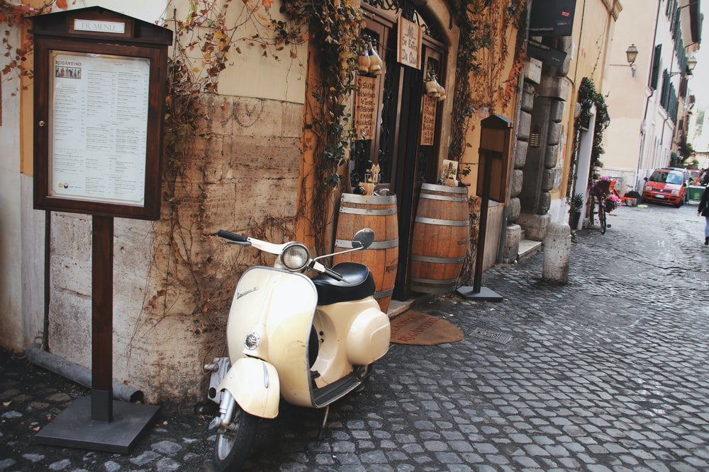 white motor scooter parked beside brown wooden door