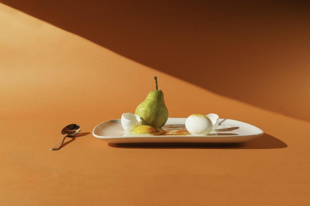 green fruit on white ceramic plate
