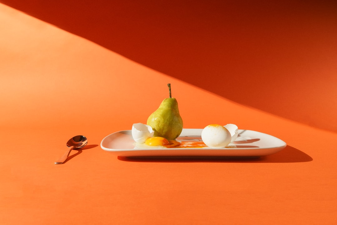 A pear and eggs with a simple orange background