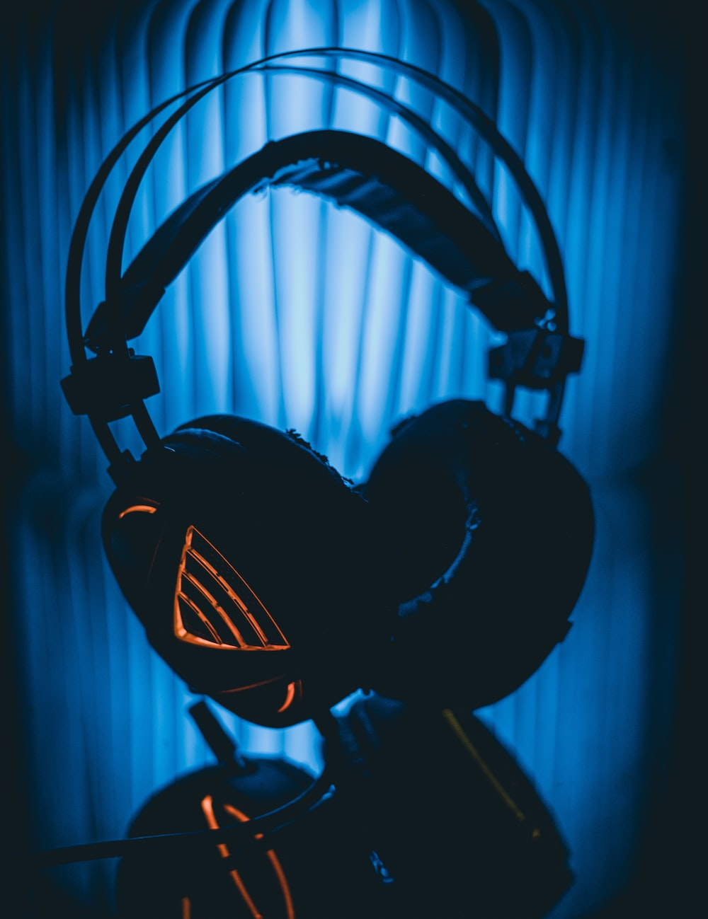 black and gray headphones on black and blue background
