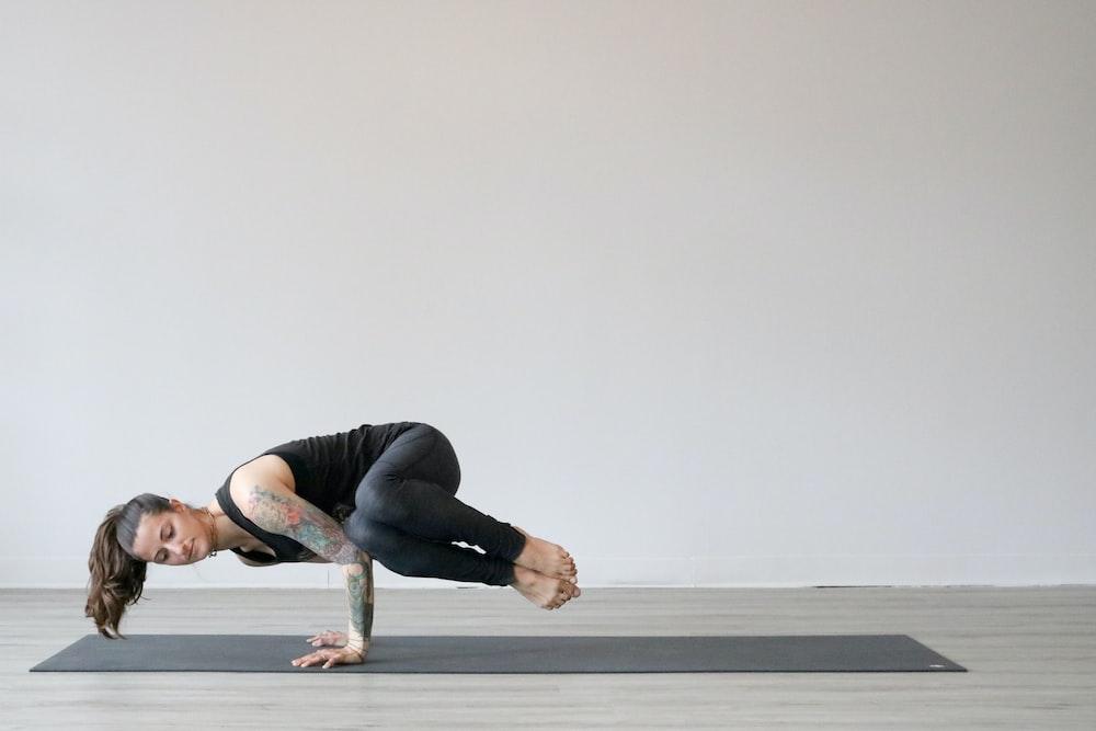 woman in black tank top and gray leggings doing yoga