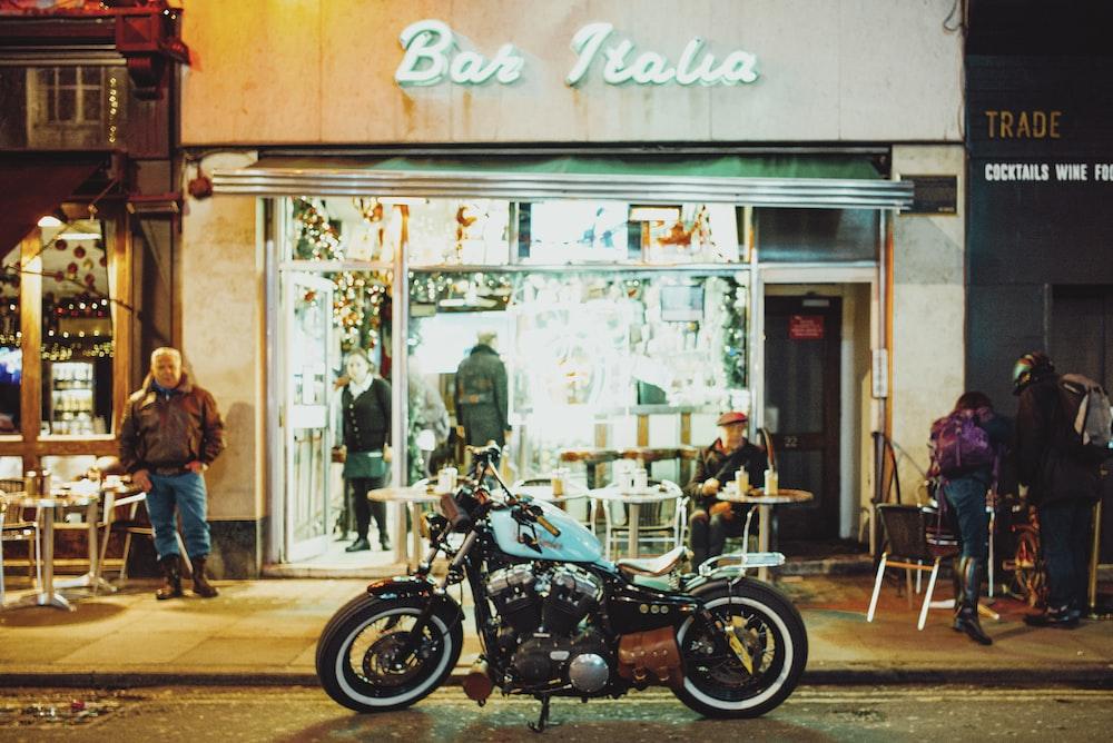 man in black jacket standing beside black motorcycle