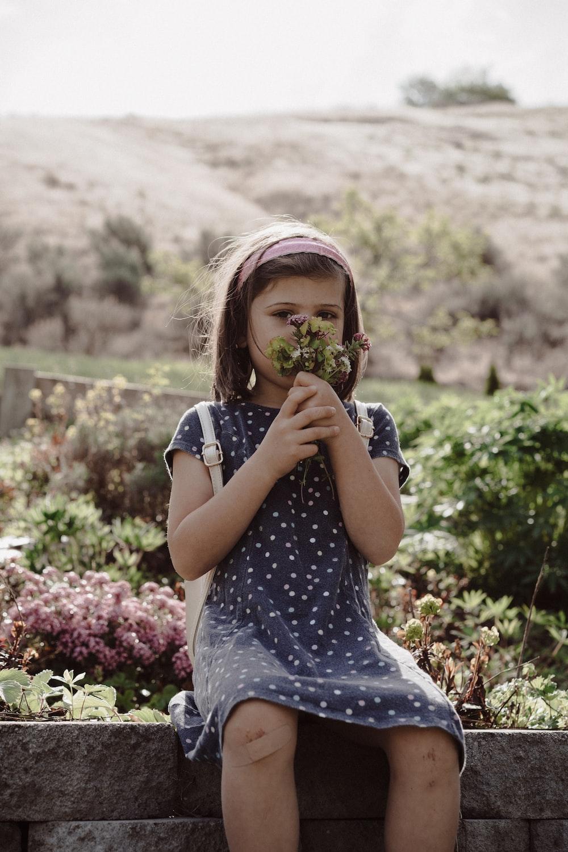 girl in blue and white polka dot dress eating fruit