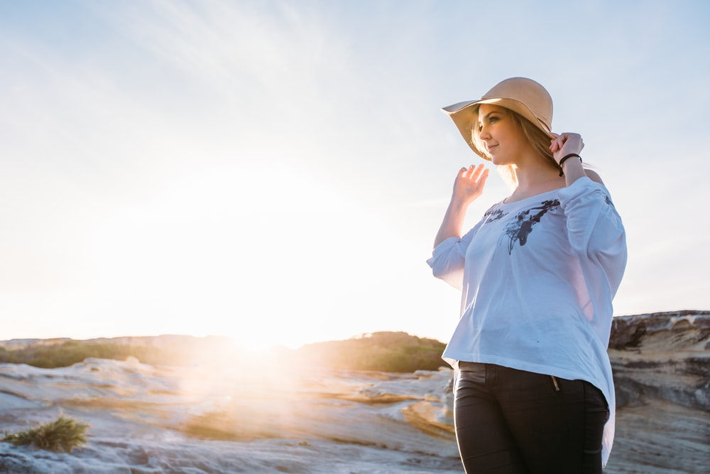 woman in blue shirt and black pants wearing brown fedora hat standing on seashore during daytime