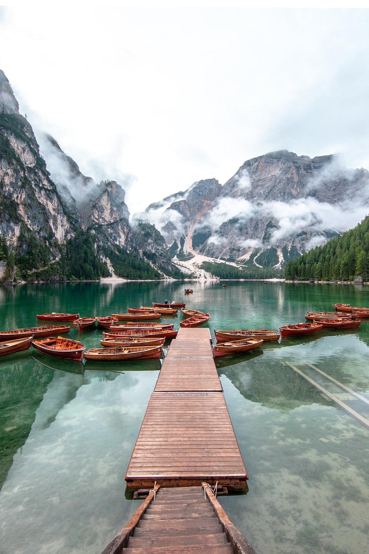 brown wooden dock on lake near mountain during daytime